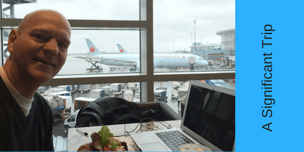 this is a picture of author Dom Kotarski at YVR airport with a Canada Air plane seen through the window of the airport
