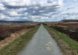 picture of a gravel path and blue sky with scattered clouds