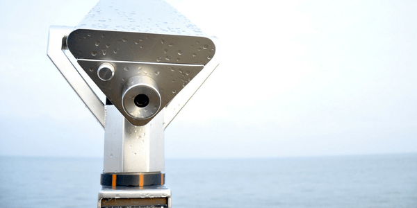 the picture shows a picture of a telescope that is pointed towards the ocean's horizon as if inviting you to look through the eye peice
