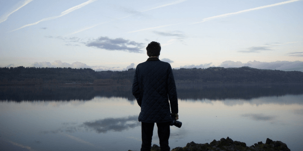 a siluette of a man looking out over a serene body of water holding a camera in his right hand
