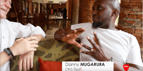 A screenshot showing Danny Mugarura and Dominic Kotarski sitting on a couch in the lobby of Kampala Serena Hotel