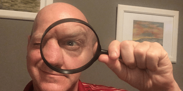 a picure showing Dominc looking through a magnifying glass