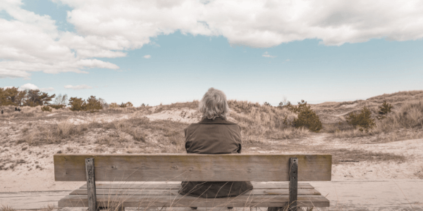 A picture of a gentleman with long grey hair sitting on a bench facing a beautiful desert> He appears to be in deep contemplation